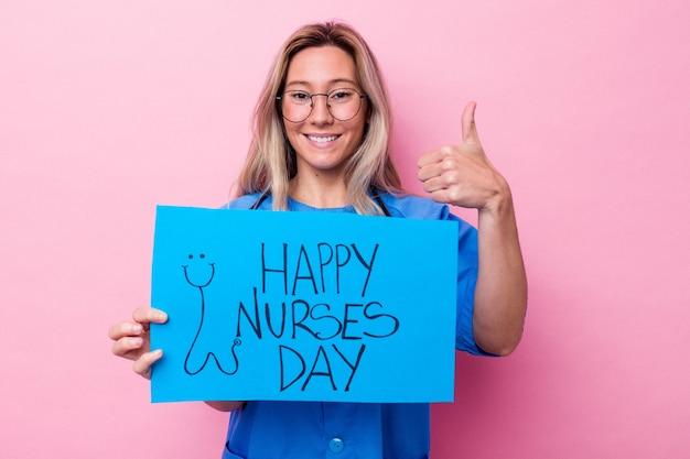 Jonge australische verpleegstersvrouw die een aanplakbiljet van de internationale verpleegstersdag houden dat op blauwe achtergrond wordt geïsoleerd