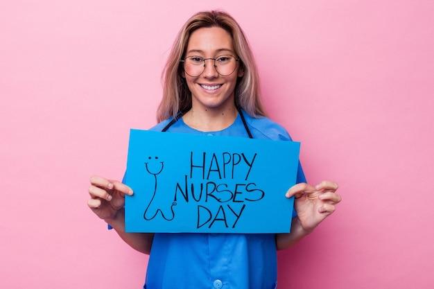 Jonge australische verpleegstersvrouw die een aanplakbiljet van de internationale verpleegstersdag houdt die op blauwe achtergrond wordt geïsoleerd