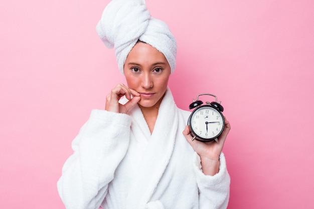 Jonge australische vrouw die de douche laat verlaat geïsoleerd op roze achtergrond met vingers op lippen die een geheim houden.
