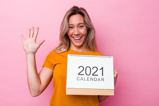 Jonge australische vrouw die een kalender houdt die op roze achtergrond wordt geïsoleerd die vrolijk glimlachen toont nummer vijf met vingers.