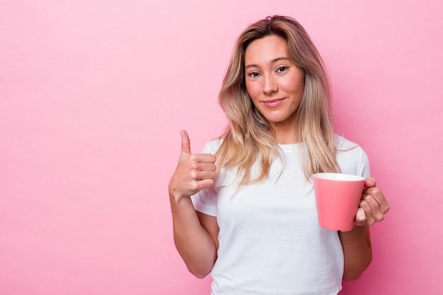 Jonge australische vrouw die een roze mok houdt die op roze achtergrond wordt geïsoleerd die en duim glimlacht opheft