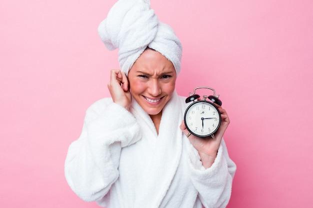 Jonge australische vrouw die laat de douche verlaat die op roze achtergrond wordt geïsoleerd die oren behandelt met handen.