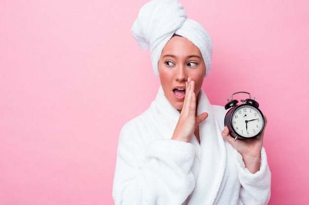 Jonge australische vrouw die laat de douche verlaat, geïsoleerd op een roze achtergrond, zegt een geheim heet remnieuws en kijkt opzij looking