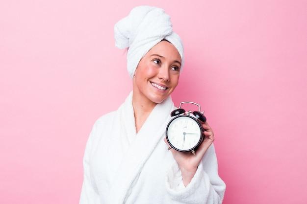 Jonge australische vrouw die laat de douche verlaat, geïsoleerd op een roze achtergrond, ziet er glimlachend, vrolijk en aangenaam uit.