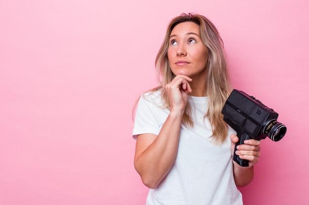 Jonge australische vrouw filmen met een vintage videocamera geïsoleerd op zoek zijwaarts met twijfelachtige en sceptische uitdrukking.