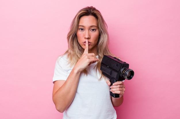 Jonge australische vrouw filmt met een vintage videocamera geïsoleerd die een geheim houdt of om stilte vraagt.