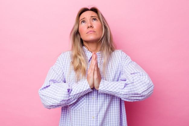 Jonge australische vrouw geïsoleerde hand in hand bid dichtbij de mond, voelt zich zelfverzekerd.