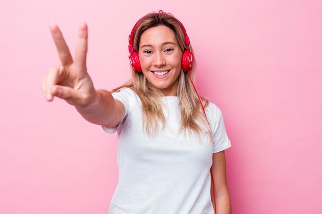 Jonge australische vrouw luisteren naar muziek geïsoleerd op roze background