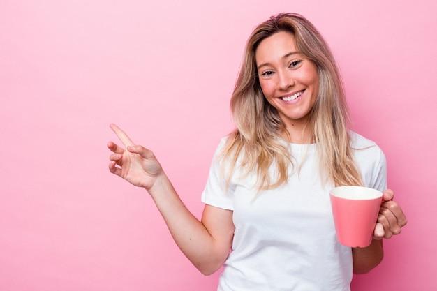 Jonge australische vrouw met een roze mok geïsoleerd op roze achtergrond glimlachend en opzij wijzend, iets tonend op lege ruimte.