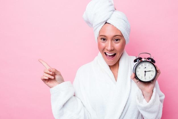 Jonge australische vrouw verlaat de douche laat geïsoleerd op een roze achtergrond die naar de zijkant wijst