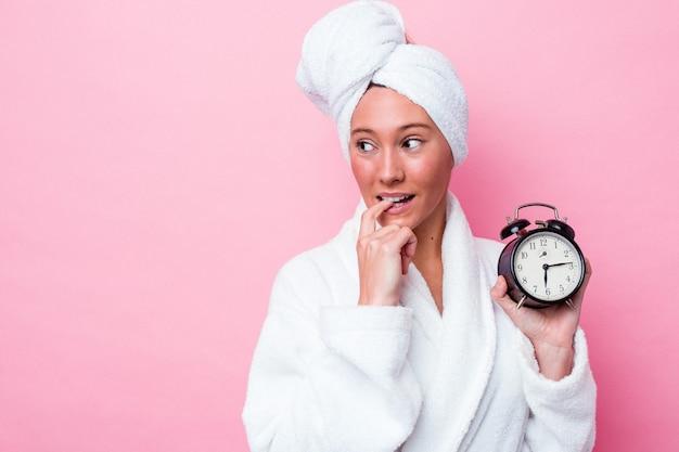 Jonge australische vrouw verlaat de douche laat geïsoleerd op roze achtergrond ontspannen denken over iets kijken naar een kopie ruimte.