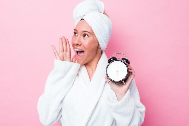 Jonge australische vrouw verlaat de douche laat geïsoleerd op roze achtergrond schreeuwen en houden palm in de buurt van geopende mond.