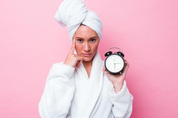 Jonge australische vrouw verlaat de douche laat geïsoleerd op roze achtergrond wijzende tempel met vinger, denken, gericht op een taak.