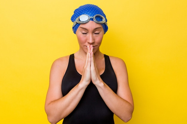 Jonge australische zwemmer vrouw geïsoleerd op gele achtergrond hand in hand bidden in de buurt van de mond, voelt zich zelfverzekerd.