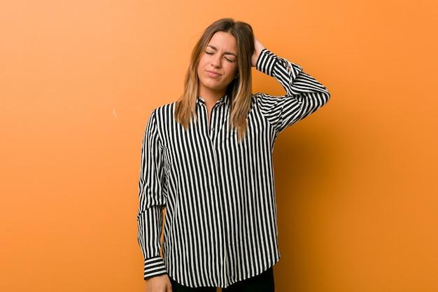 Jonge authentieke charismatische echte mensenvrouw tegen een muur die aan nekpijn lijdt vanwege een sedentaire levensstijl.