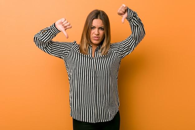 Jonge authentieke charismatische echte mensenvrouw tegen een muur die duim toont en afkeer uitdrukt.