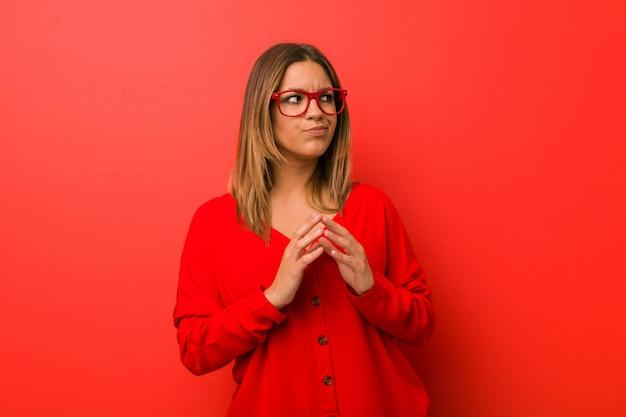 Jonge authentieke charismatische echte mensenvrouw tegen een muur die een plan bedenkt en een idee opzet.