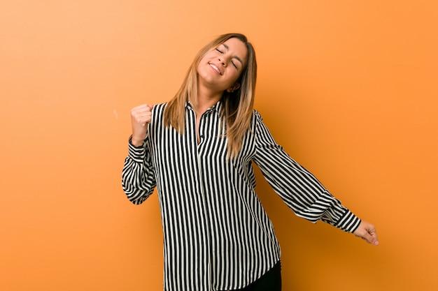 Jonge authentieke charismatische echte mensenvrouw tegen een muur die en pret dansen danst.