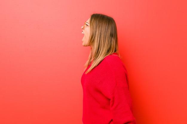 Jonge authentieke charismatische echte mensenvrouw tegen een muur die naar een exemplaarruimte schreeuwt