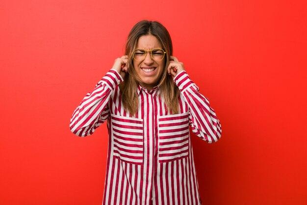 Jonge authentieke charismatische echte mensenvrouw tegen een muur die oren behandelen met handen.