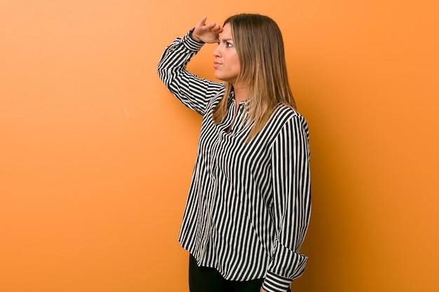 Jonge authentieke charismatische echte mensenvrouw tegen een muur die ver weg hand op voorhoofd houden.