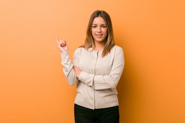 Jonge authentieke charismatische echte mensenvrouw tegen een muur die vrolijk wijzend met weg wijsvinger glimlachen.