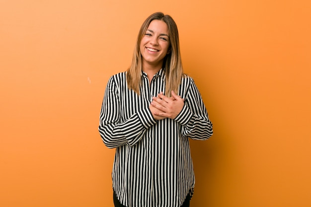Jonge authentieke charismatische echte mensenvrouw tegen een muur heeft een vriendelijke uitdrukking en drukt palm tegen borst. liefde concept.