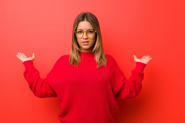 Jonge authentieke charismatische echte mensenvrouw tegen een muur maakt schaal met armen, voelt zich gelukkig en zelfverzekerd.