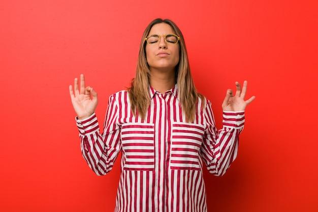 Jonge authentieke charismatische echte mensenvrouw tegen een muur ontspant na een zware werkdag, ze beoefent yoga.