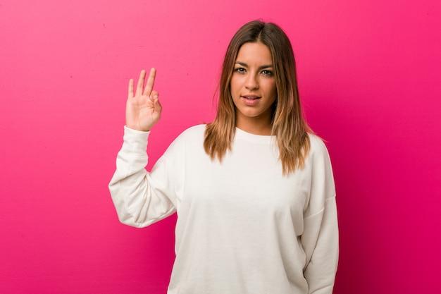 Jonge authentieke charismatische echte mensenvrouw tegen een muur vrolijk en zeker tonend ok gebaar.