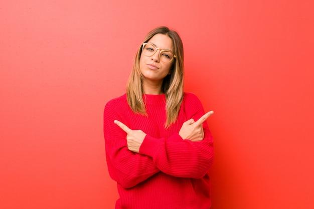 Jonge authentieke charismatische echte mensenvrouw tegen een muur wijst zijwaarts, probeert te kiezen tussen twee opties.