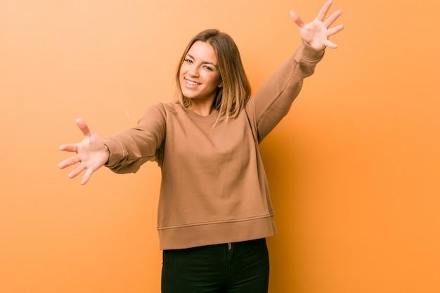 Jonge authentieke charismatische vrouw tegen een muur voelt zich zelfverzekerd en geeft een knuffel