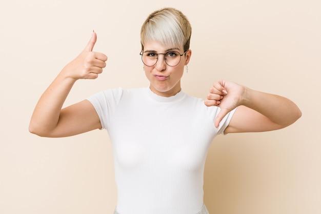 Jonge authentieke natuurlijke vrouw die een wit overhemd draagt dat duimen omhoog en duimen toont