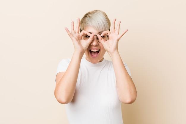 Jonge authentieke natuurlijke vrouw die een wit overhemd draagt dat ok teken over ogen toont