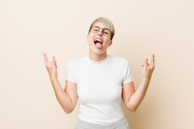 Jonge authentieke natuurlijke vrouw die een wit overhemd draagt dat rotsgebaar met vingers toont