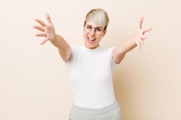 Jonge authentieke natuurlijke vrouw die een wit shirt draagt, voelt zich zelfverzekerd en geeft een knuffel