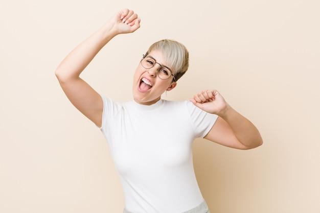 Jonge authentieke natuurlijke vrouw draagt een wit shirt dat een speciale dag viert, springt en heft armen met energie