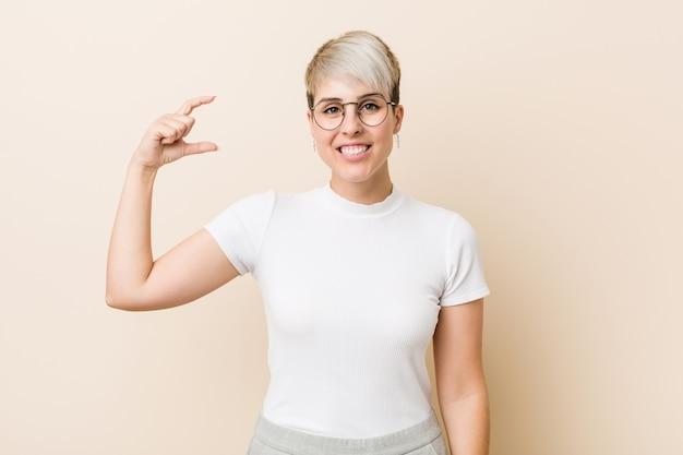 Jonge authentieke natuurlijke vrouw draagt een wit shirt met iets kleins met wijsvingers, glimlachend en zelfverzekerd.
