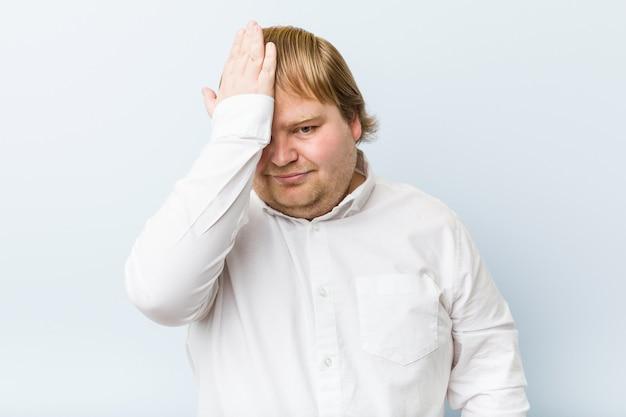 Jonge authentieke roodharige dikke man die iets vergeet, op het voorhoofd slaat met de palm en de ogen sluit.