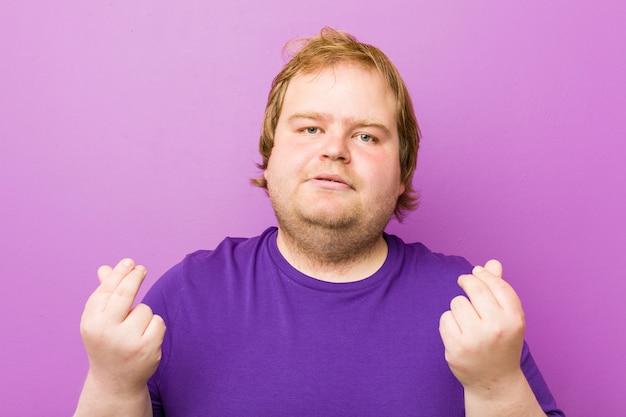 Jonge authentieke roodharige dikke man die laat zien dat ze geen geld heeft.