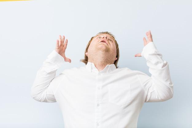 Jonge authentieke roodharige dikke man die naar de hemel schreeuwt, gefrustreerd opkijkend.