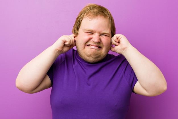 Jonge authentieke roodharige dikke man die oren bedekt met handen.