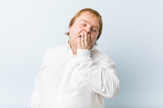Jonge authentieke roodharige dikke man geeuwt met een moe gebaar kegelvormige mond met hand.