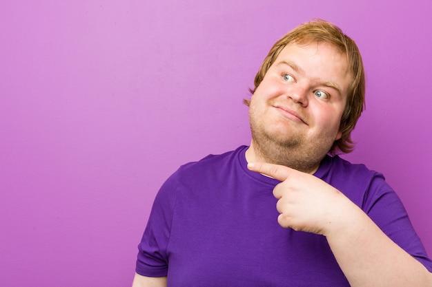 Jonge authentieke roodharige dikke man glimlachend vrolijk wijzend met wijsvinger weg.
