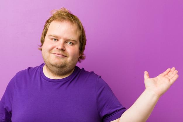Jonge authentieke roodharige dikke man toont een kopie ruimte op een palm en houdt een andere hand op de taille.