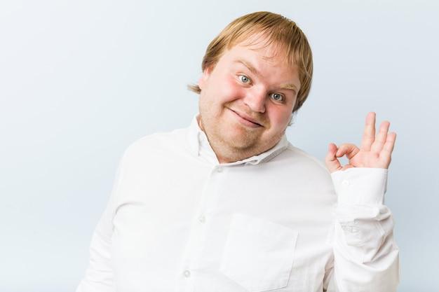 Jonge authentieke roodharige dikke man vrolijk en zelfverzekerd met ok gebaar.