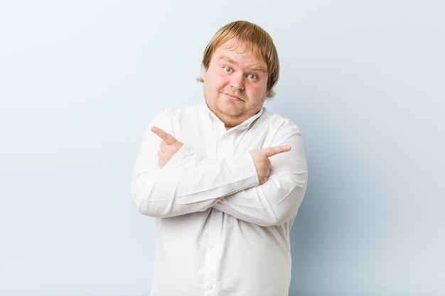 Jonge authentieke roodharige dikke man wijst zijwaarts, probeert te kiezen tussen twee opties.