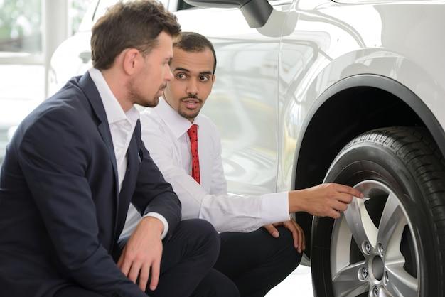 Jonge autoverkoper die de voordelen van de auto toont.