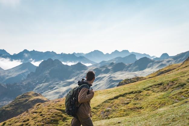 Jonge avontuurlijke jongenstrekking in de hoge bergen lifestyle ontspannen en vrijheid