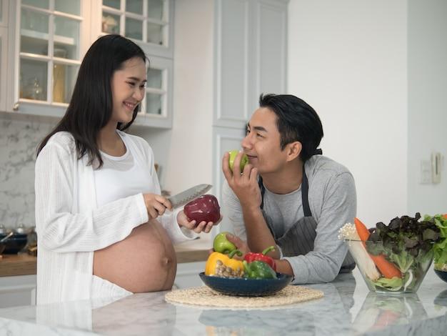 Jonge aziaat die het zwangere paar koken samen in de keuken thuis verwachten.